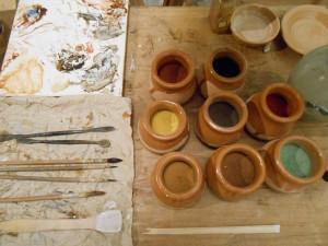 Vasetti contenenti pigmenti, tavolozza ricoperta di pergamena ingessata, spatole in metallo, spatola in legno per la manipolazione della biacca, pennelli di vaio.